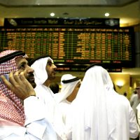 Abu Dhabi, UNITED ARAB EMIRATES:  Emirati and Arab men discuss the stock rates at the Abu Dhabi Stock Market 14 March 2006. Share markets in the oil-rich Gulf states, including the Saudi bourse -- the largest in the Arab world -- dived further today.The Saudi Tadawul All-Shares Index (TASI) dropped for the fourth day running, shedding 4.82 percent to end below the 15,000-point psychological barrier for the first time this year at 14,887.74 points. AFP PHOTO/STR  (Photo credit should read STR/AFP/Getty Images)